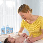 Mutter mit ihrem neugeborenem Baby betreibt Säuglingspflege an der Wickelkommode, freigestellt vor weißem Hintergrund.